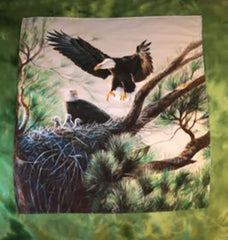 Quilt with eagles in a nest surrounded by a green border.