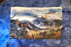 Quilt features bald eagles soaring over green mountains.