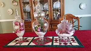Dining Room table center piece with quilt runner and decorated apothecary jars made by Jackie Vujcich of Colorado Creations Quilting