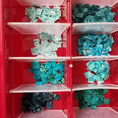 Tiny aqua blue half-inch squares separted by color in an ornament container.