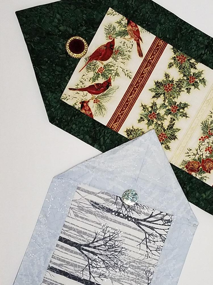 Two table runners for the holidays.  One has cardinals and green borders while the other has silver trees with blue borders.  Both fabric kits are available at Colorado Creations Quilting