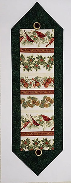 Cardinals surrounded by green border table runner quilt kit available at Colorado Creations Quilting.