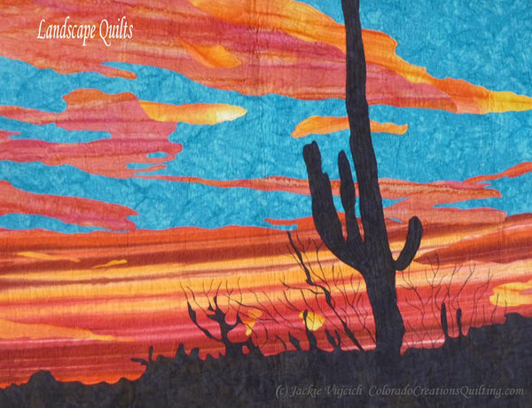 Saguaro Sunset quilt pattern by Jackie Vujcich of Colorado Creations Quilting  features a silhouette of the cactus with a blue and orange sunset in the background.