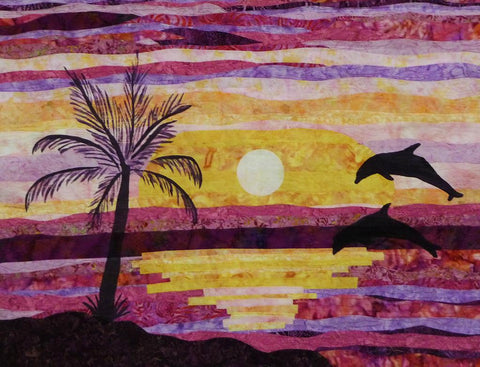 Dancing Dolphins quilt shows a silhouette of a palm tree and two dolphins jumping out of the water in front of a setting sun. Available at Colorado Creations Quilting
