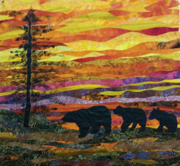 Evening Stroll landscape quilt shows a silhouette of an evergreen tree and three bears strolling with a golden sunset above.  Available at Colorado Creations Quilting