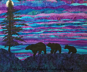 Evening Stroll landscape quilt shows a silhouette of an evergreen tree and three bears strolling in front of a rising moon.  Available at Colorado Creations Quilting