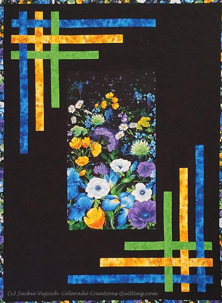 Quilt center of blue, green, and purple flowers on a background of black with yellow, blue and green strips woven in the borders.  Pattern available at Colorado Creations Quilting