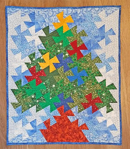 Just in time for the holiday season, this one of a kind quilted wall hanging features a Christmas tree with ornaments and a star on top on a blue background Available at Colorado Creations Quilting