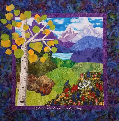 Colorado Escape landscape quilt pattern shows purple mountains in the distance with green rolling hills and wildflowers and an aspen tree in the foreground by Colorado Creations Quilting