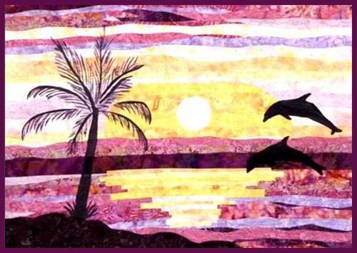 Dancing Dolphins Landscape Mixed Media Quilt Kit features 2 dolphins jumping out the ocean with a palm tree in the foreground.  All the sunset-colored fabric is also displayed
