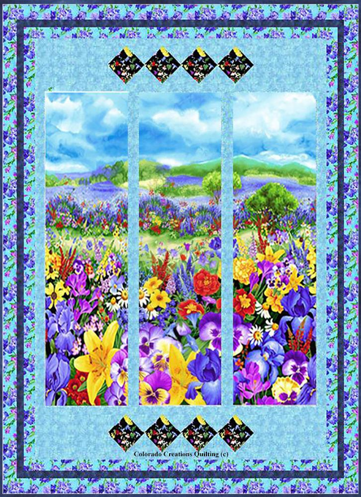 Display of all  fabrics needed for the Wild Meadow quilt kit available at Colorado Creations Quilting.  Fabrics feature a panel with a meadow of brightly colored wild flowers, iris on a blue background, and blender navy and aqua blues.