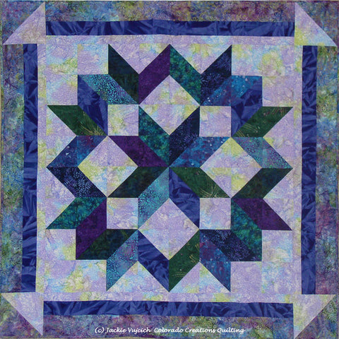 Capenter Wheel Star quilt  in blues & purples on a light blue background with a dark blue border available at Colorado Creations Quilting