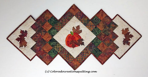Fall Harvest table runner has a center square set on point with an appliques pumpkin on it.  Additional borders and applique maple leaves surround the center.