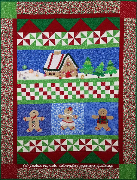 Sugar & Spice row quilt in pieced blocks of red/green/white and appliques of gingerbread people and houses on a blue background available at Colorado Creations Quilting