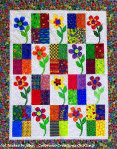 Flower Power Quilt:alternates pieced 4-patch squares and appliqued flower on white background with a surrounding border available at Colorado Creations Quilting