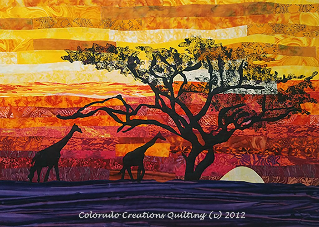 Two giraffes in silhouette strolling passed a moonlit tree, a orange/red/yellow sunset sky and all the fabric needed to complete the quilt top.  Across the Serengeti quilt kit available at Colorado Creations Quilting.
