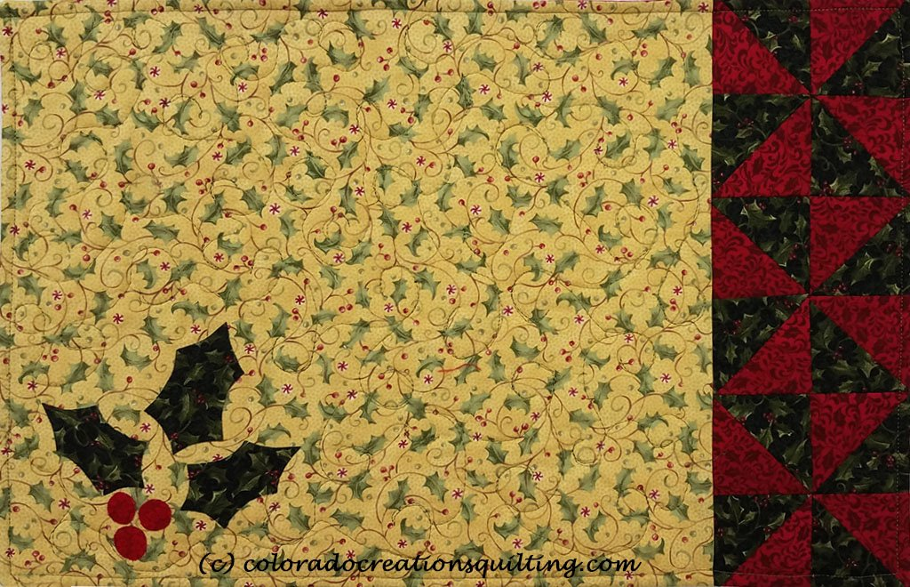 Cream colored placemats with holly leaves applique and green and red triangles on one edge