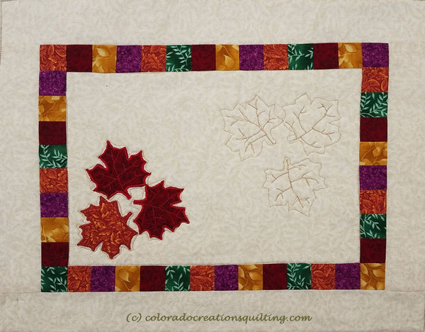 Fall Leaves quilted placemat has a cream center square with three applique maple leaves on it.  Additional small squares border and another cream border surround the center.