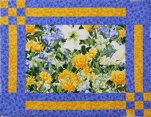 Placemats have a main flower fabric in the center with gold and blue lattice borders on the edges