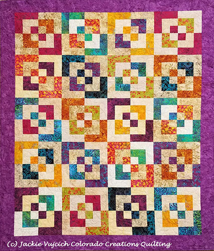 Expolding Blocks quilt shows broken square multi-olored blocks on a light background with a violet border available at Colorado Creations Quilting