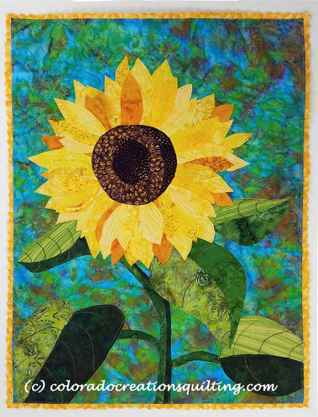 One sunflower on a blue background.  Quilt pattern available at Colorado Creations Quilting