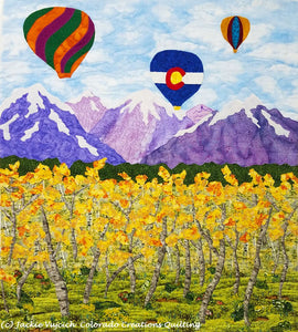 Soaring Over the Rockies Quilt shows 3 hot air balloons flying over snowcapped mountain peaks.  Aspens turning yellow are in the meadow below. Available at Colorado Creations Quilting