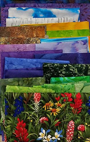 Display of all  fabrics needed for the Colorado Escape quilt kit available at Colorado Creations Quilting.  Fabrics feature richly-colored batiks and an amazing wildflower print.