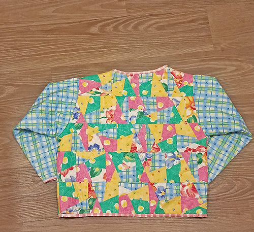 This darling quilted one of a kind jacket (back side) in florals and pastels will definitely make a statement! Available at Colorado Creations Quilting