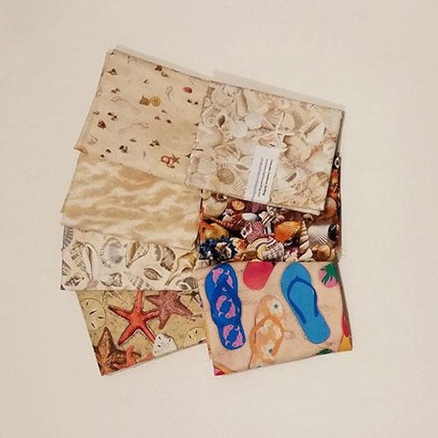 This fat quarter bundle has a selection of seashells and sand fabrics