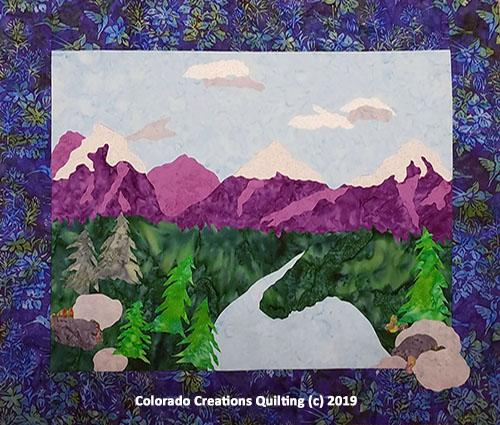Purple mountain scene with a river flowing into the lake below.  Improv Landscape quilt pattern by Jackie Vujcich of Colorado Creations Quilting