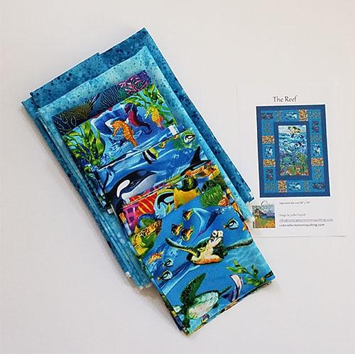 The Reef quilt pattern by Jackie Vujcich is a tribute to life under the sea. Start with a wonderful fabric panel by Timeless Treasures and add in coral, sea turtles, sea horses, killer whales, tropical fish and more. Panel and coordinateing blocks are surrounded by blue borders. This kit shows all the fabric included along with the pattern. Available at Colorado Creations Quilting