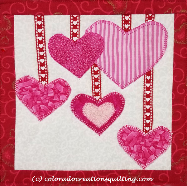 Pink hearts appliqued on a quilted square to hold your coffee cup