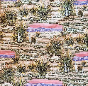 Blooming yucca on the desert floor with a backdrop of purple mountains and a sunset sky cotton fabric. Available at Colorado Creations Quilting