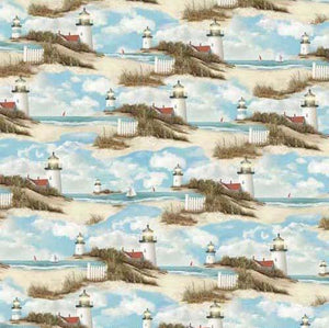 Images of serene lighthouses, sailboats and white beach fences are featured on a background of blue skies above blue ocean waters. Available at Colorado Creations Quilting