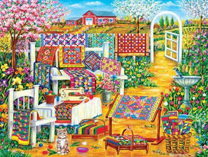 "This jigsaw puzzle by SunsOut in Puzzles and Games item #50514 has 500 pieces and features an lovely garden with a birdbath and white fence and bench covered in brightly-colored quilts. Finished size 18"" x 24"""""
