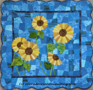 Quilt shows appliqued dresden plate sytle sunflowers on a blue background