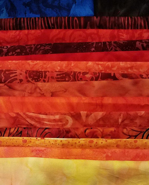 Display of all  fabrics needed for the Stand Off quilt kit available at Colorado Creations Quilting.  Fabrics feature richly-colored reds, golds and oranges.  The makings of a sunset sky.