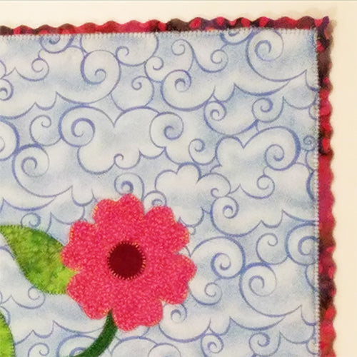 Close up view of scalloped edging on a small art quilt