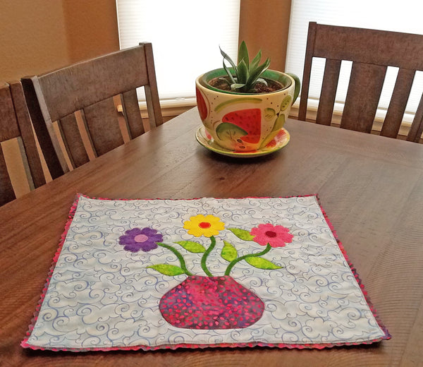 This darling little one of a kind art quilt features a flower pot with three brightly colored daisies on a blue background with a unique edging. Available at Colorado Creations Quilting