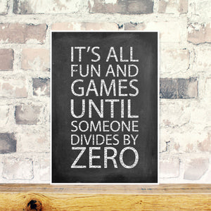 Chalkboard print with the words 'it's all fun and games until someone divides by zero' on a brick background