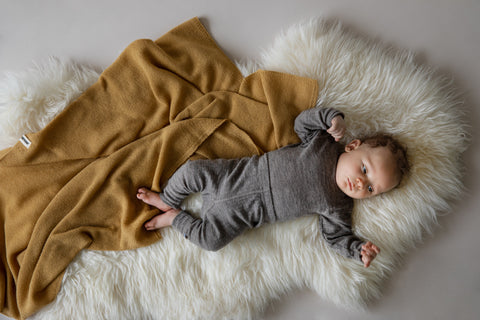 A baby lying on a lambswool with a merino wool blanket