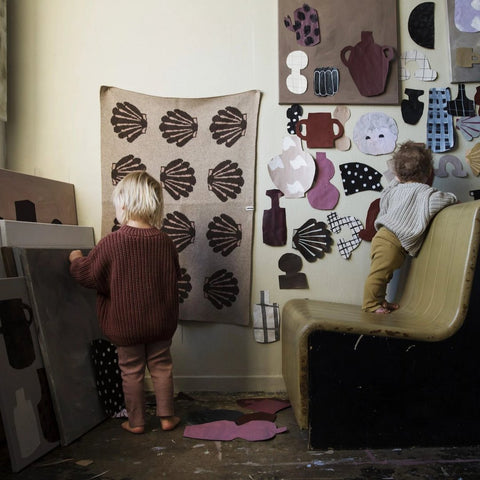 Two toddlers playing in a studio with Emilia Ilke x Jordling Home wool blankets