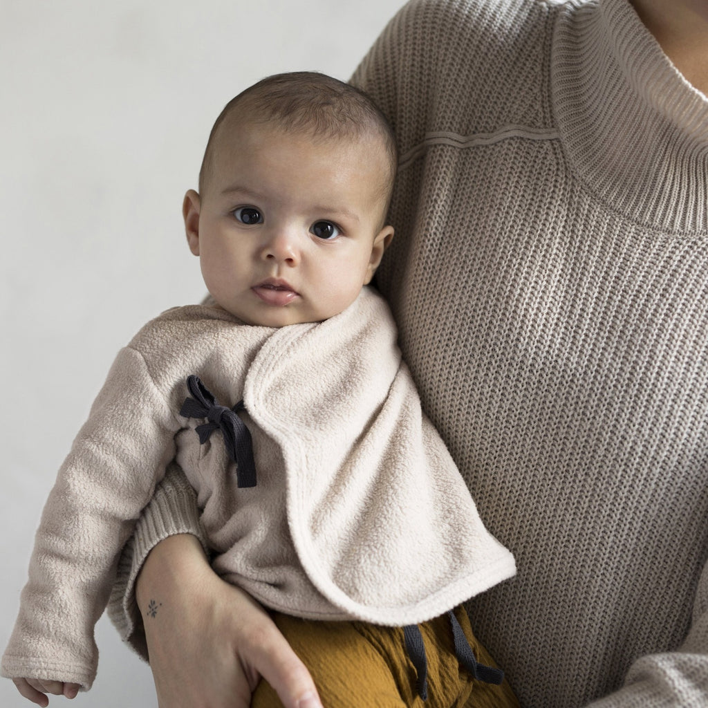 A small baby on their mother's lap wearing Teddy baby cardigan by sustainable kidswear brand Phil&Phae