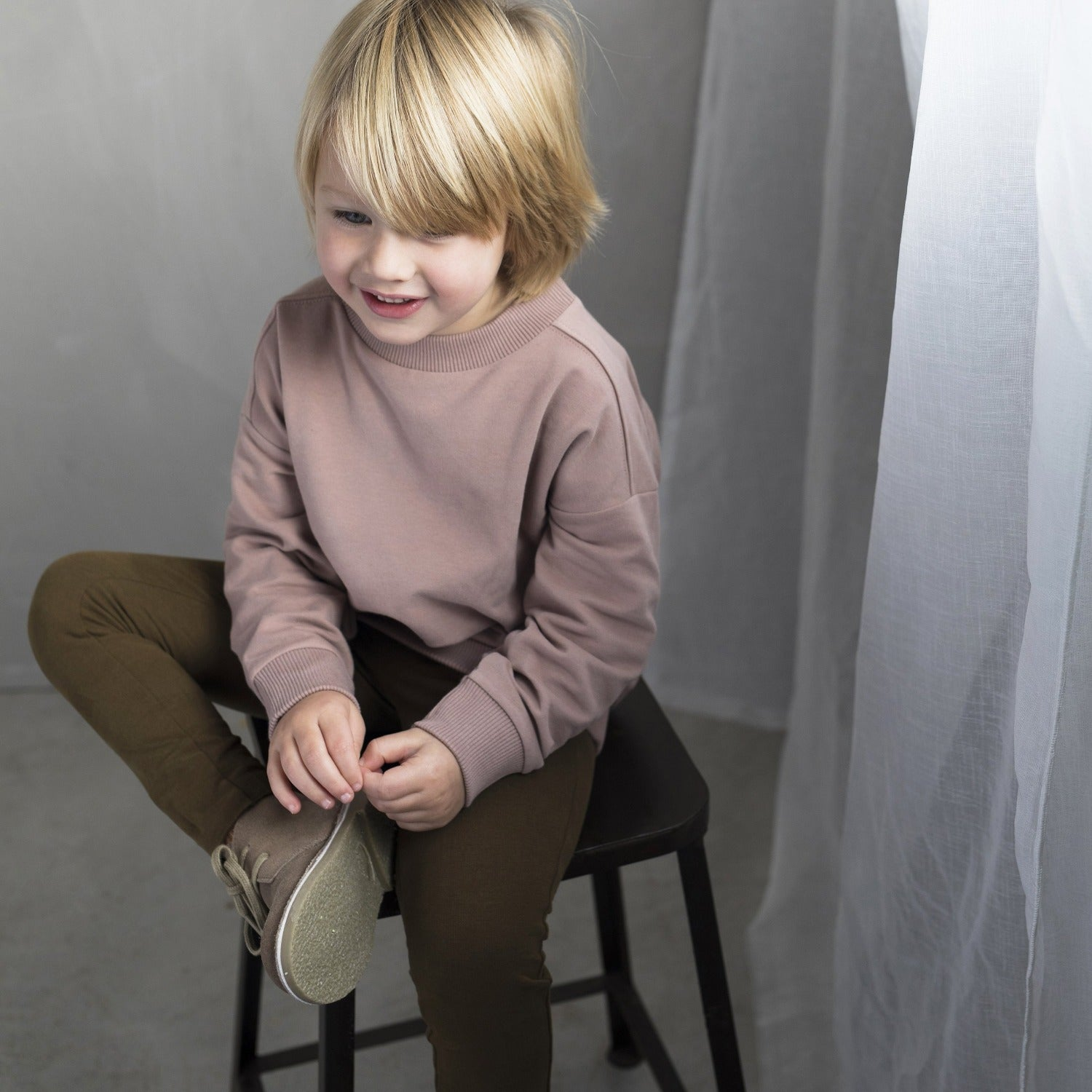 A little boy wearing the Oversized Sweater colour Powder by sustainable kidswear brand Phil&Phae