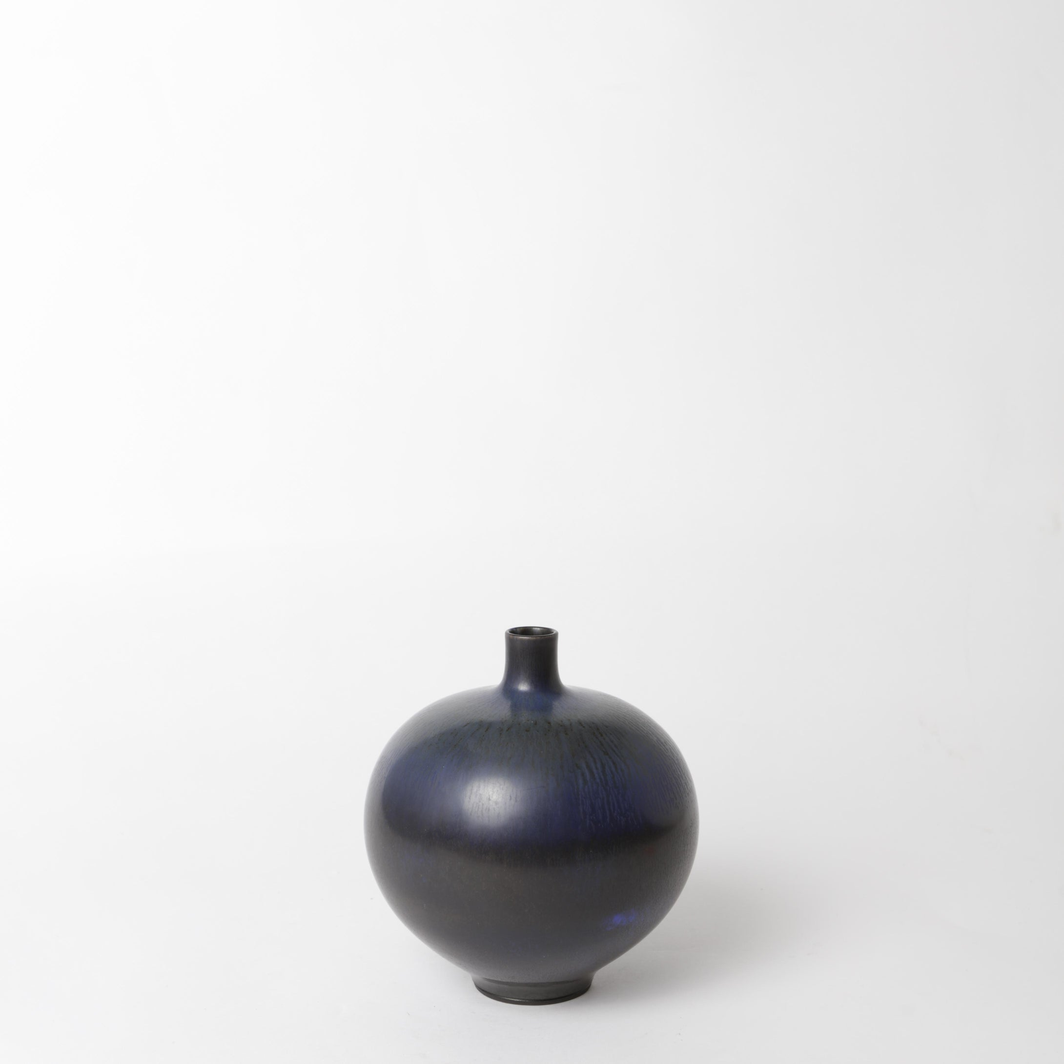 "Stengodsvas från Gustavsberg år 1958 av Berndt Friberg, med harpälsglasyr. Signerad Friberg Ö samt Studiohanden. 16cm hög. Stoneware vase by Berndt Friberg 1958 for Gustavsberg. Harefur glaze. Signed Friberg Ö and the ""Studio Hand"" H: 16cm/6,3″"
