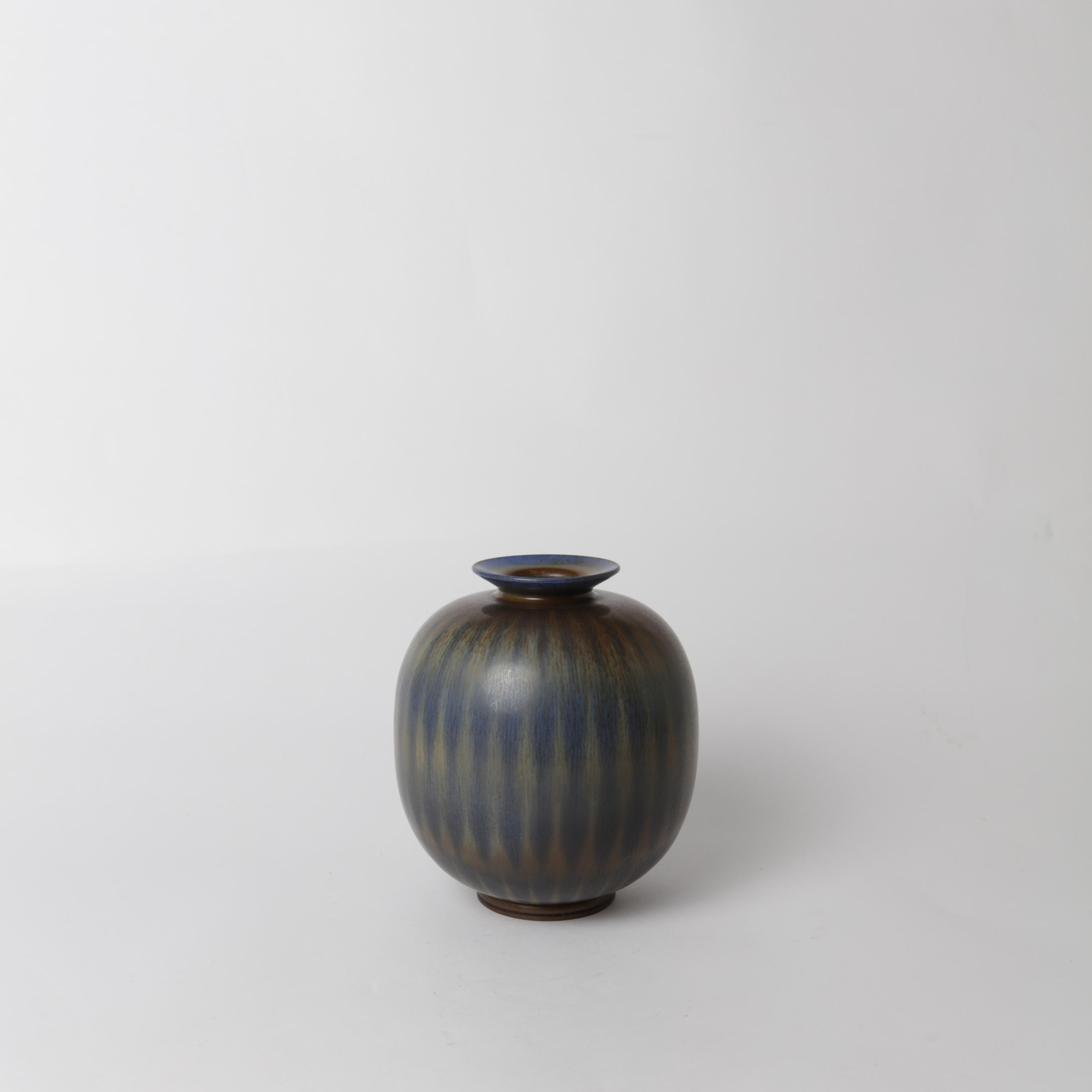 Stengodsvas av Berndt Friberg år 1960 för Gustavsberg med harpälsglasyr. 17,5cm hög. Signerad Friberg b samt Studiohanden. Stoneware vase by Berndt Friberg 1960 for Gustavsberg. Harefur glaze. H: 17,5cm/6,9″. Signed Friberg b and the