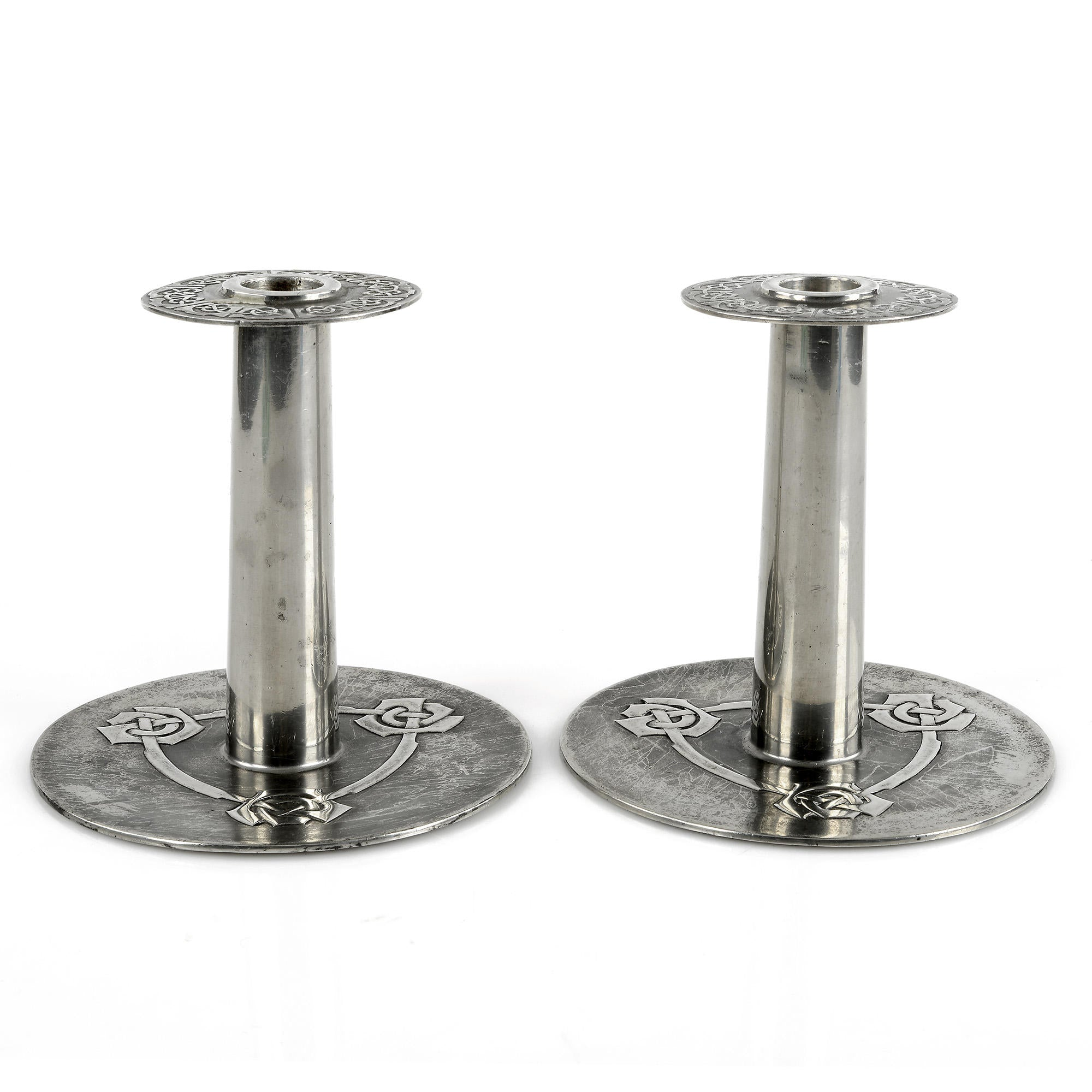 Paret Liberty & Co Tudric tennljusstakar av Archibald Knox i Keltisk stil. H: 15,5cm. Märkta Tudric 08. Pair of Liberty & Co Tudric pewter candle sticks by Archibald Knox with Celtic knot frieze. H: 15,5cm/6,1