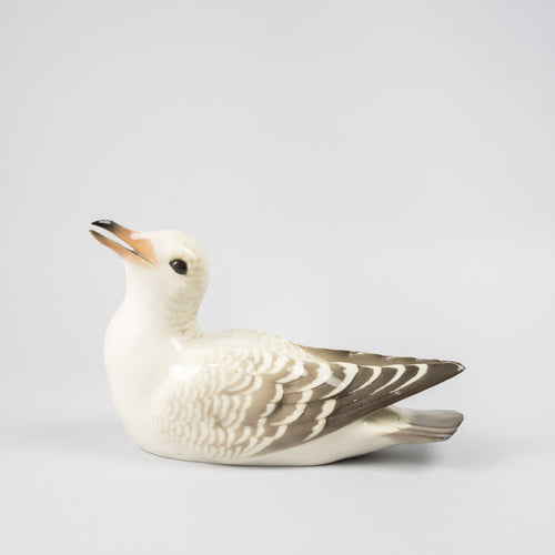 Mås i underglasyrteknik, 1920-tal. Tillverkad på Rörstrand och såld hos Löfbergs i Malmö. 11,5cm hög och 19cm lång. Gull in porcelain painted with underglazed technic, 1920's. Made by Rörstrand. H: 11,5cm/4,5