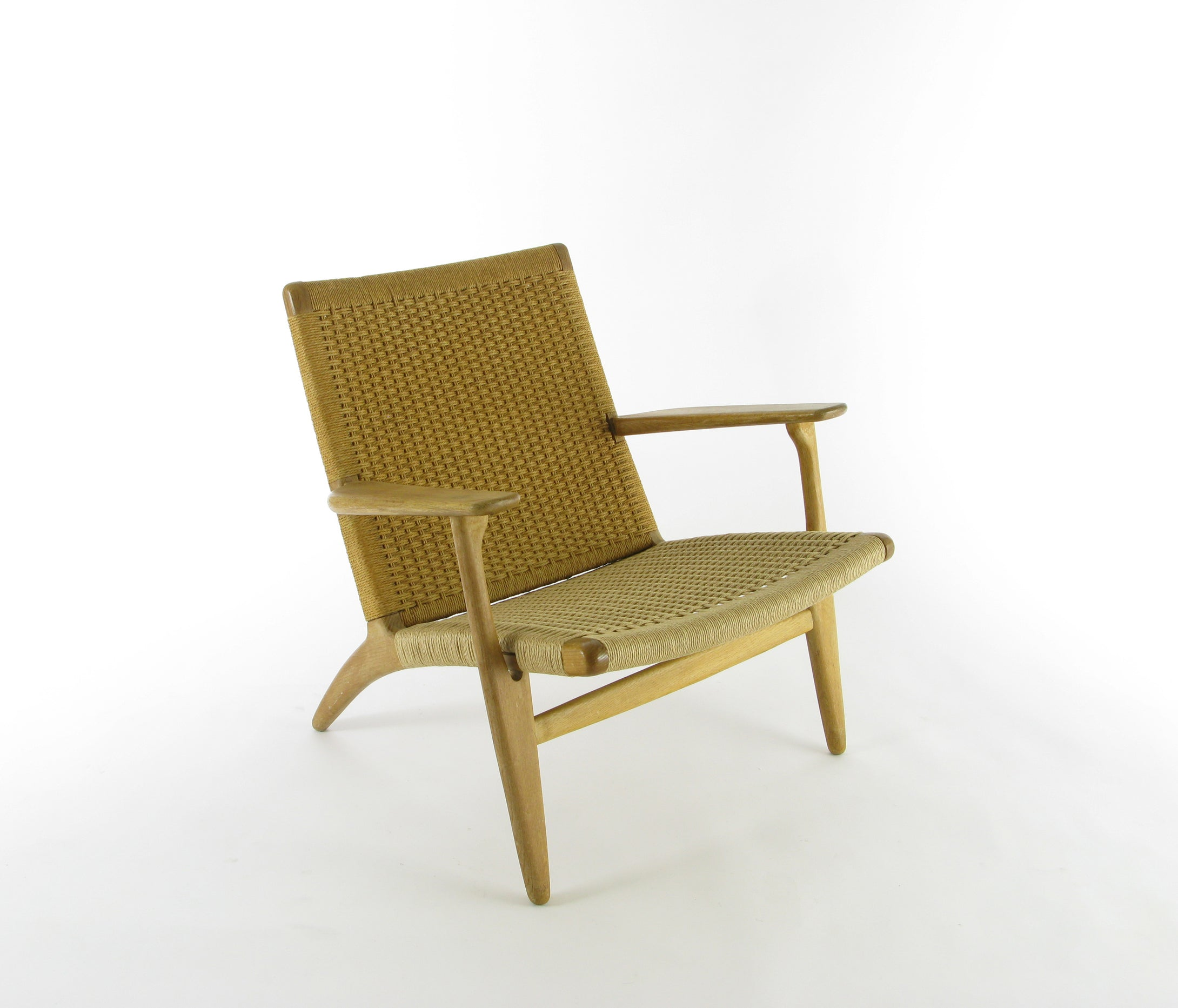 Fåtölj CH25 av Hans Wegner för Carl Hansen & Son. Ek samt snörad rygg och sits. Sitsen är nysnörad. H: 71cm, B: 70cm, D: 75cm. Etikettmärkt. Hans Wegner lounge chair CH25 for Carl Hansen & Son. Oak and natural cord. New seating cord. H: 71cm/28