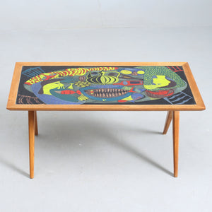"Soffbord, med benställning i ek, av David Rosén för NK, med skiva i polykrom emalj av Stig Lindberg för Gustavsberg, 1950-tal. 107cm X 57cm och 43cm högt. Signerat Stig L. Stig Lindberg polychrome enamel coffee table with oak base by David Rosén for NK, 1950's. 107cm/42,1"" X 57cm/22,4"" and H: 43cm/16,9"". Signed Stig L."